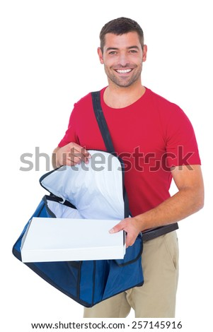 Portrait of happy delivery man removing pizza box from bag on white background