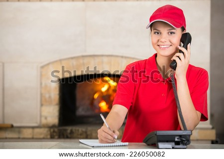 Portrait of happy delivery woman of pizza holding pen and diary for placing order by phone. - stock photo