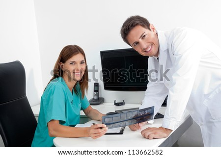Portrait of happy dentist and female assistant analyzing X-ray report at office desk - stock photo