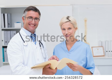 Portrait of happy doctor and nurse holding report in clinic