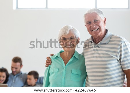 Portrait of happy elderly couple smiling at camera - stock photo