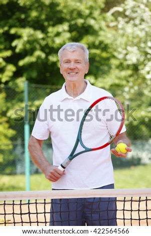 Portrait of happy elderly man with tennis racket and ball standing at net on tennis court. - stock photo