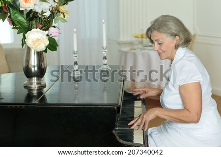 Portrait of happy elderly woman playing the piano at home - stock photo