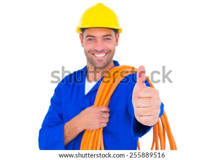 Portrait of happy electrician with rolled wire gesturing thumbs up on white background - stock photo