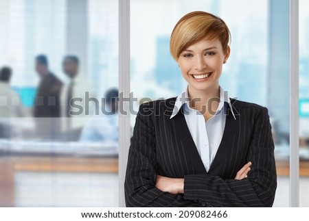 Portrait of happy elegant businesswoman at office, copyspace on left. - stock photo