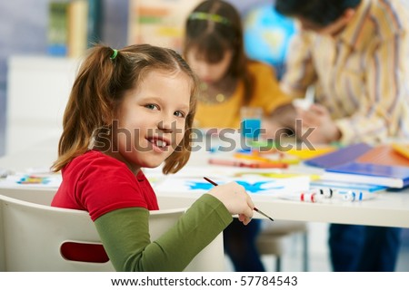Portrait of happy elementary age child sitting at desk looking at camera in art class in primary school classroom, smiling.? - stock photo