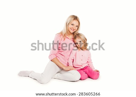 Portrait of happy embracing mother and daughter sitting on the floor - stock photo
