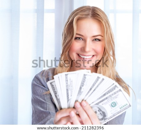 Portrait of happy excited woman holding in hands many dollars, at home, financial success, spending money, wealth concept - stock photo
