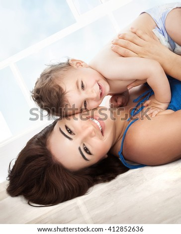 Portrait of happy faces, young family with pleasure spending time together at home, mother playing with her precious little son