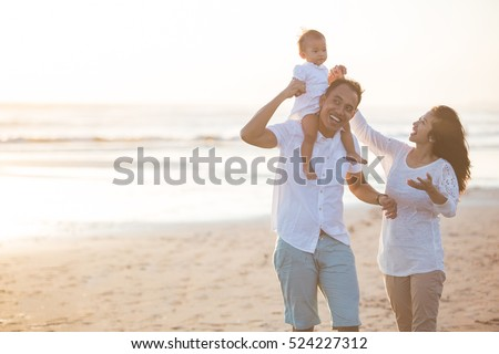 portrait of happy family and baby enjoying sunset in the summer leisure