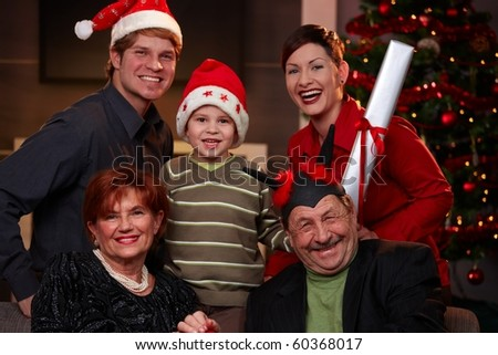 Portrait of happy family at christmas eve. Father and son wearing Santa Claus hat, smiling.? - stock photo