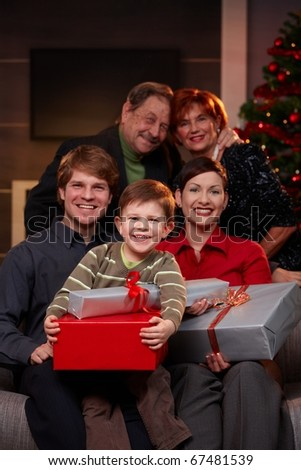 Portrait of happy family at christmas eve, holding presents, smiling. - stock photo
