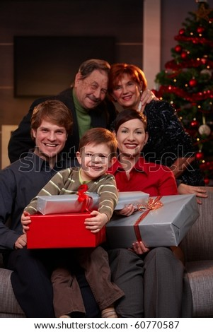 Portrait of happy family at christmas, sitting on sofa, holding presents, smiling.? - stock photo