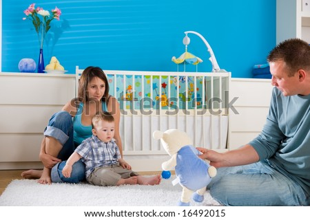 Portrait of happy family at home. Baby boy ( 1 year old ) and young parents father and mother sitting on floor and playing together at children's room, smiling. - stock photo