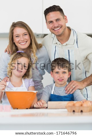Portrait of happy family baking cookies together at counter in kitchen
