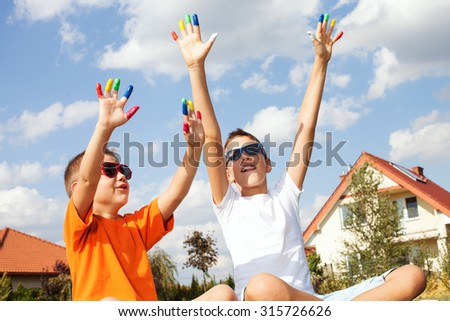 Portrait of happy family. Beautiful mother with two young sons enjoying sunny day, lying on the grass. - stock photo