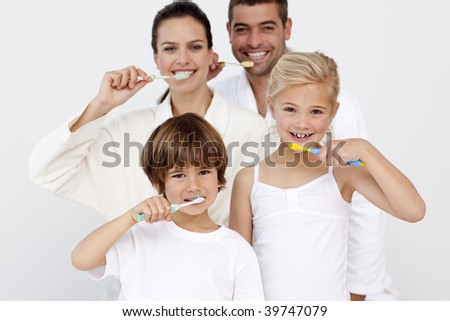 Portrait of happy family cleaning their teeth in bathroom - stock photo