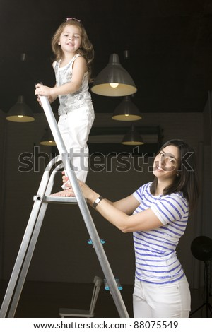 portrait of happy family doing repair, little daughter on ladder - stock photo