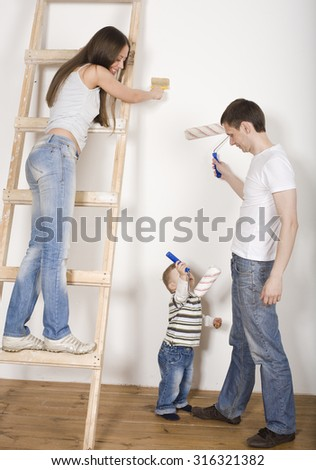 portrait of happy family doing repair, new house painting walls - stock photo