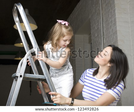 portrait of happy family doing repair, standing on ladder - stock photo