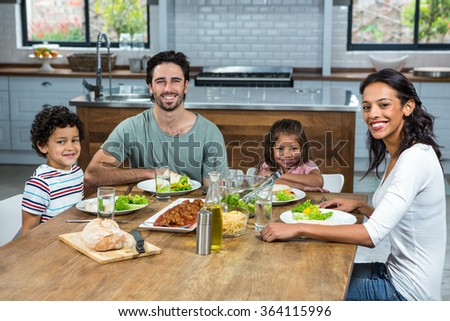 portrait of happy family eating together in the kitchen - stock photo