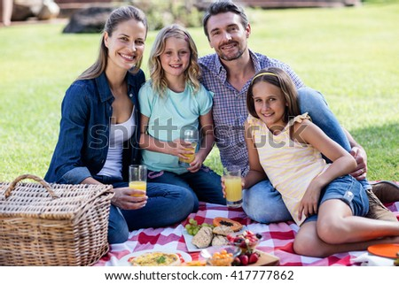 Portrait of happy family having a picnic in the garden
