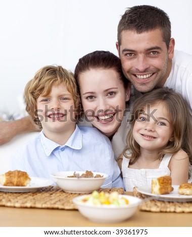 Portrait of happy family having breakfast in kitchen - stock photo