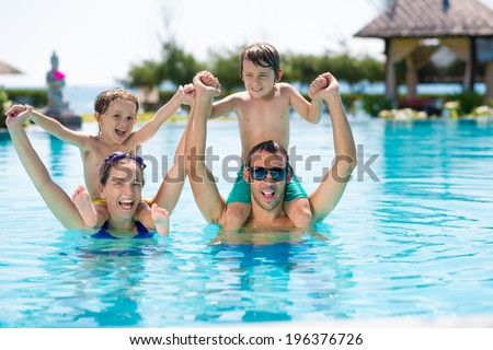 Portrait of happy family having fun in the swimming pool - stock photo