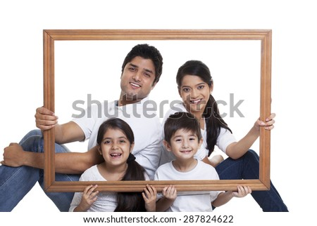 Portrait of happy family holding frame - stock photo