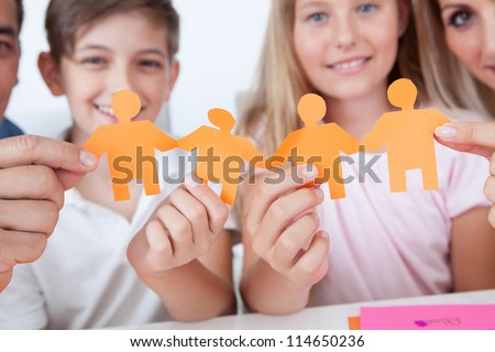 Portrait Of Happy Family Holding Paper People In Hand At Home - stock photo