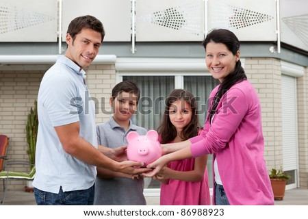Portrait of happy family holding piggy bank outside their house - stock photo