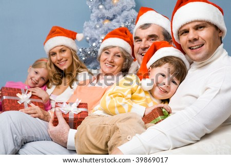 Portrait of happy family in Santa caps on Christmas Eve