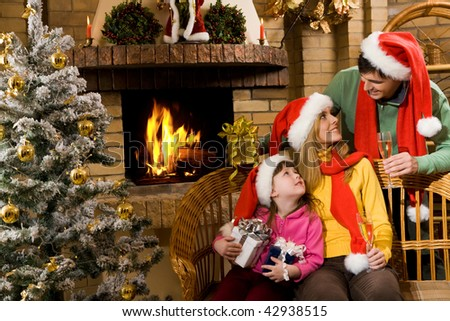 Portrait of happy family in santa caps sitting by fireplace and looking at each other