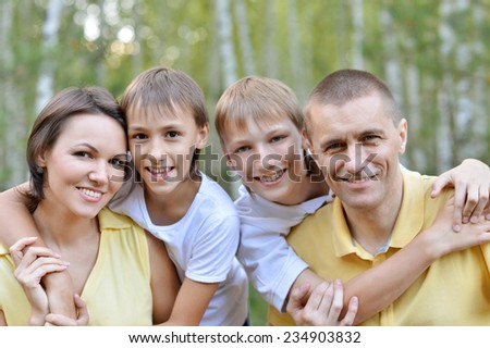 Portrait of happy family in the park - stock photo
