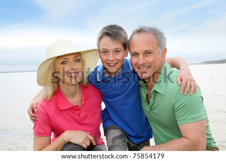Portrait of happy family kneeling by a lake - stock photo