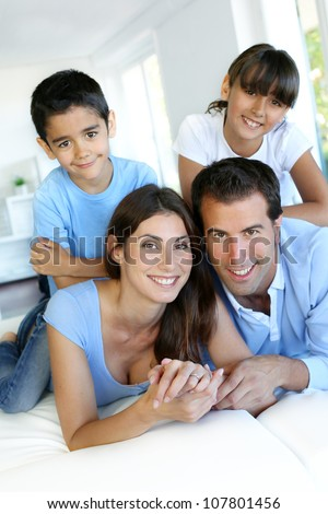 Portrait of happy family laying down bed - stock photo