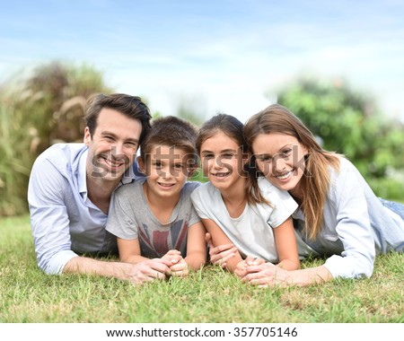 Portrait of happy family laying down in grass - stock photo