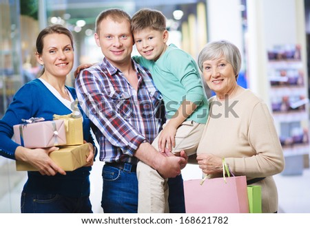Portrait of happy family looking at camera after shopping - stock photo