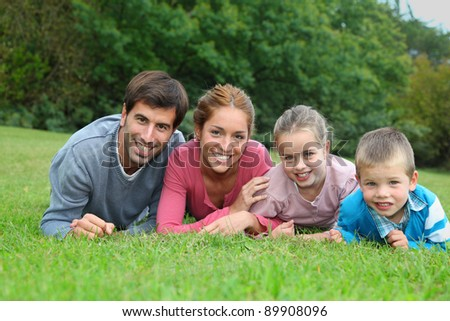 Portrait of happy family lying down in grass - stock photo