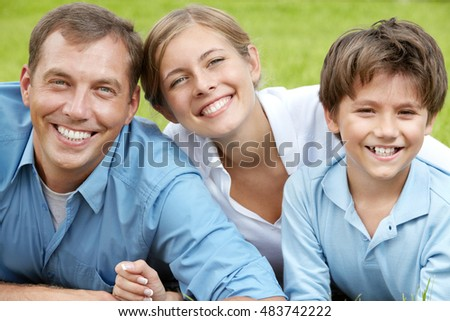 Portrait of happy family lying in grass, looking at camera and smiling
