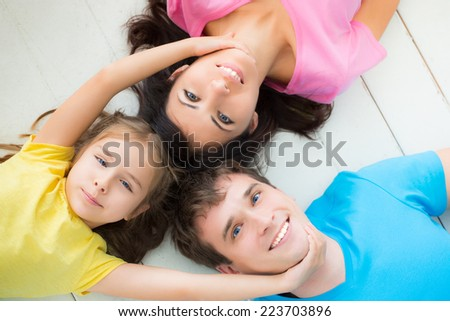 Portrait of happy family lying on floor. Father, mother and child having fun at home - stock photo