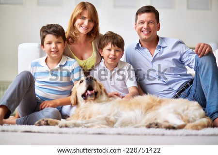 Portrait of happy family members and restful dog - stock photo
