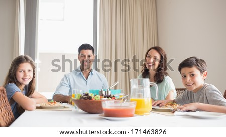Portrait of happy family of four sitting at dining table in the home - stock photo