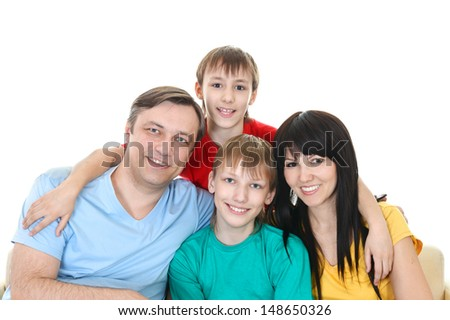 portrait of happy family of four together at home