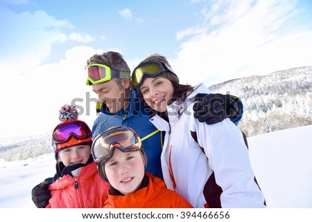 Portrait of happy family of 4 in snowy mountains