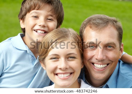 Portrait of happy family of three looking at camera and smiling