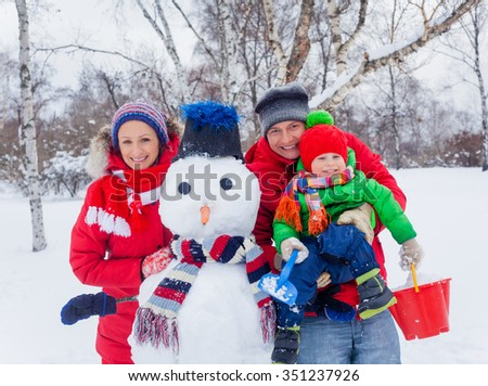 Portrait of Happy family of three making a snowman - stock photo