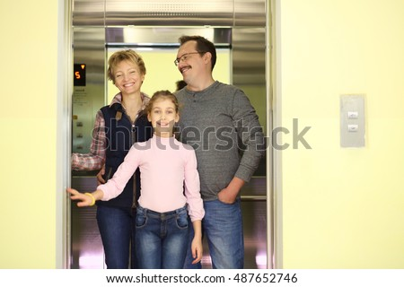 Portrait of happy family of three people in the elevator