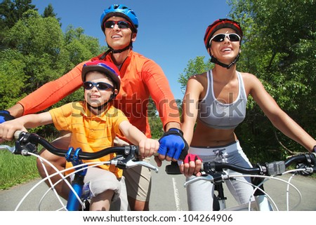 Portrait of happy family on bicycles in the park