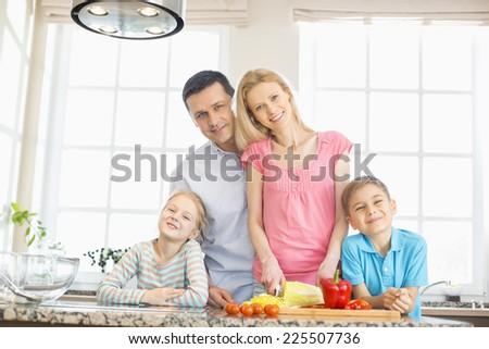 Portrait of happy family preparing food in kitchen - stock photo